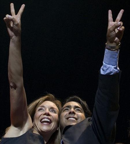 """Saludo doble. Enríquez-Ominami, junto a su esposa, Karen Doggenweiler, saludaron a sus adherentes invitándolos a marcar el número 2 en el voto presidencial, o tal vez simplemente, en un acto de optimismo, señalando la """"v"""" de la victoria."""
