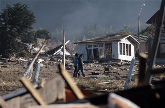 Dos hombres caminan entre las casas arruinadas hoy-lunes 8 de marzo de 2010-en la localidad de Iloca