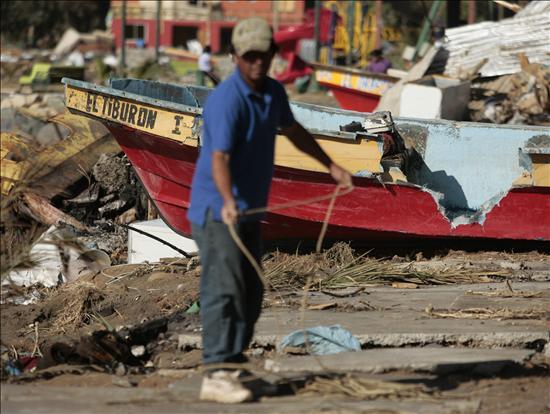 Pescador recoge cuerdas delante de su bote averiado-lunes 8 de marzo de 2010- en Caleta Duao