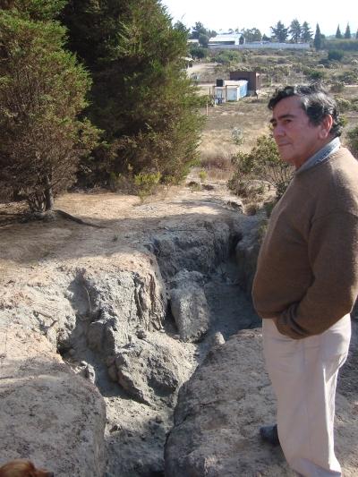 Rafael Sánchez vive en Campiche hace 28 años. Está de pie sobre el cerro de cenizas que está contiguo a su casa y que fue abandonado por una termoeléctrica.