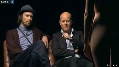 En el show, dos hombres comentan sobre el cuerpo de una mujer desnuda.