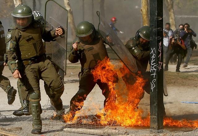 El lado B de la marcha: encapuchados queman auto y lanzan molotov a carabinero