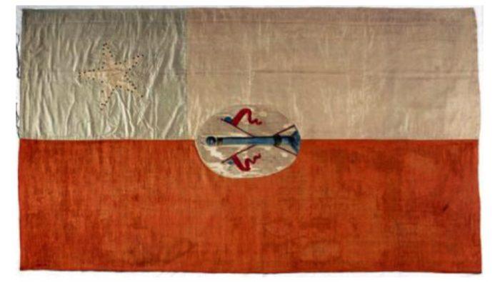 Fotografía de la bandera de la independencia tal cual es conservada hoy en el museo. No está de más decir que ninguna de las restauraciones a las que ha sido sometida ha tenido especial cuidado de su innegable valor geométrico, de modo que sus dimensiones actuales son diferentes a las de su concepción original.