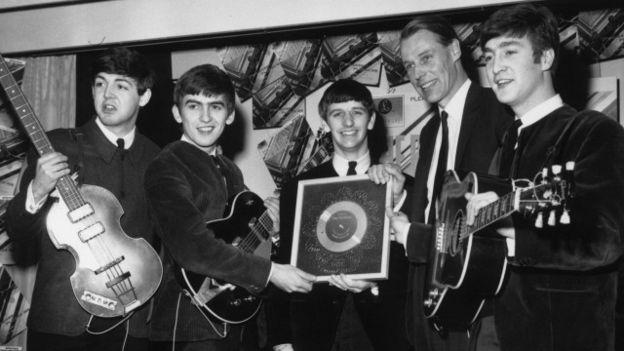 George Martin y los Beatles en una imagen de 1963 con un disco de platino.