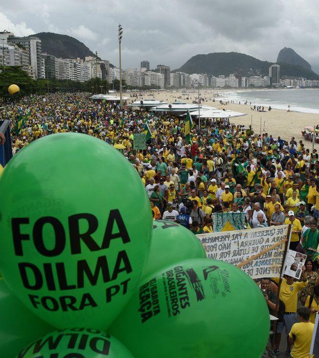 """En Río de Janeiro, la manifestación se desarrolló en Copacabana. Gran parte de los manifestantes llevaron banderas verdes y amarillas y vistieron ropa de esos colores. Algunos globos decían: """"Fuera Dilma""""."""