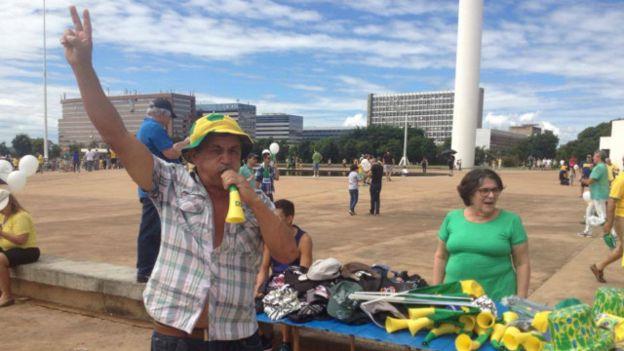 Antonio de Souza, de 60 años, ha visto las cuatro manifestaciones contra el gobierno que se han celebrado desde marzo de 2015. Su misión es vender gorras, banderas y cornetas.