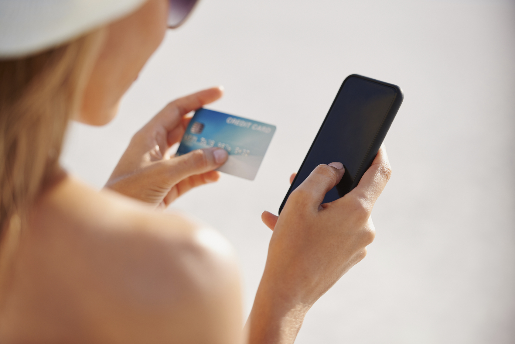 Woman using credit card on vacation shopping online with mobile phone at the beach
