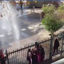 Estudiantes de la UDP se arrodillan delante del carro lanzaaguas en medio de incidentes