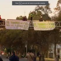 Manifestantes de La Pintana reclaman contra proyecto urbano del Gobierno arriba de señalética en Vicuña Mackenna