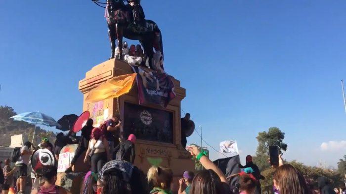 8M: hombres encapuchados intentaron tumbar estatua de Baquedano en medio de manifestaciones