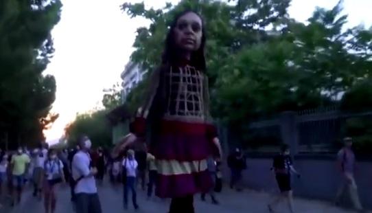 Marioneta gigante que representa a una niña refugiada de Siria camina por las calles de Europa como parte de una intervención artística